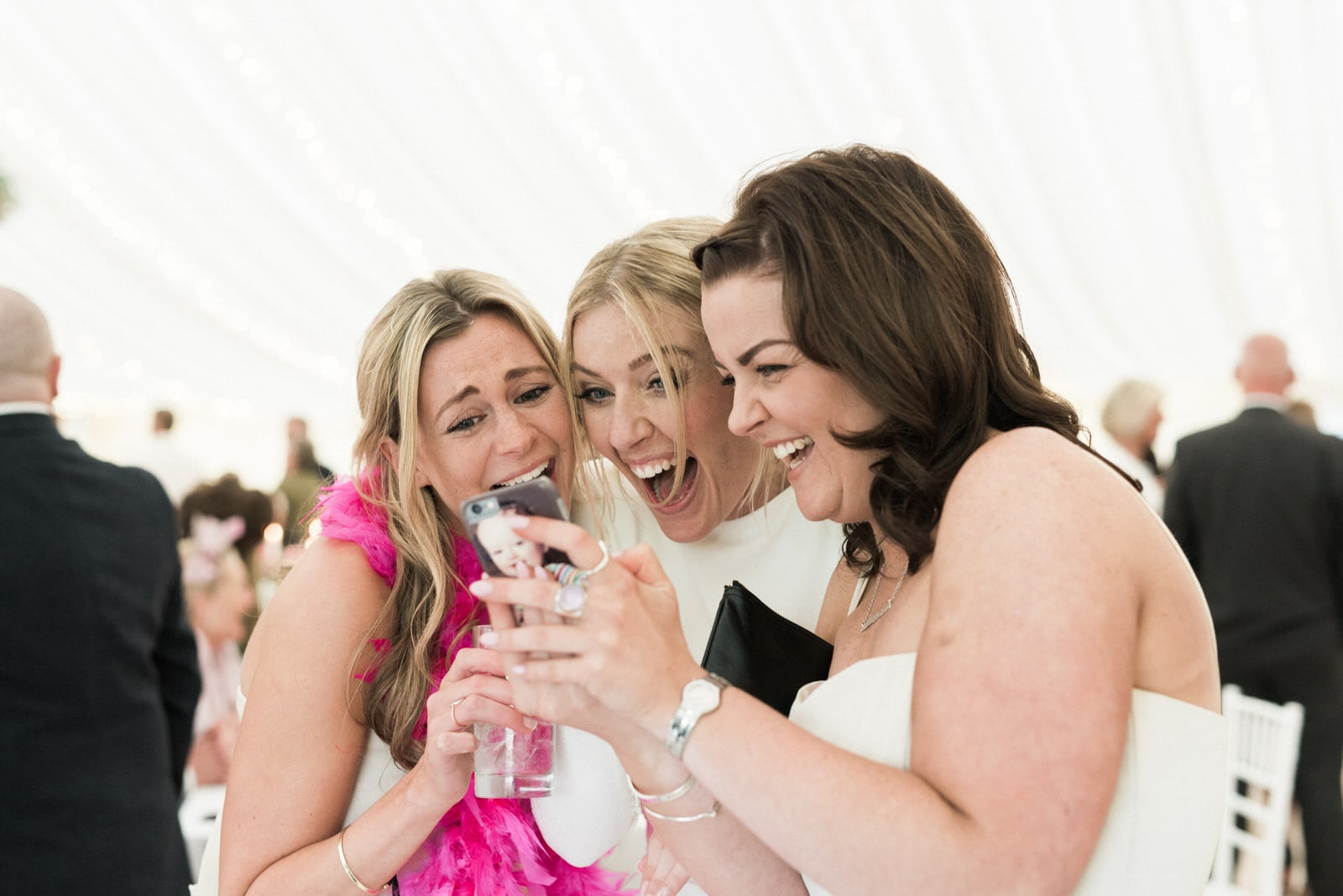bride and bridesmaids laughing at phone