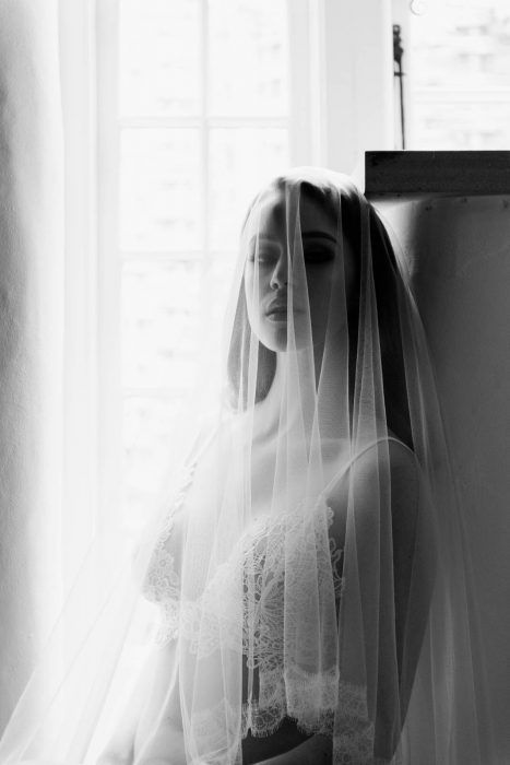 Bride sat in window with wedding veil and bridal lingerie
