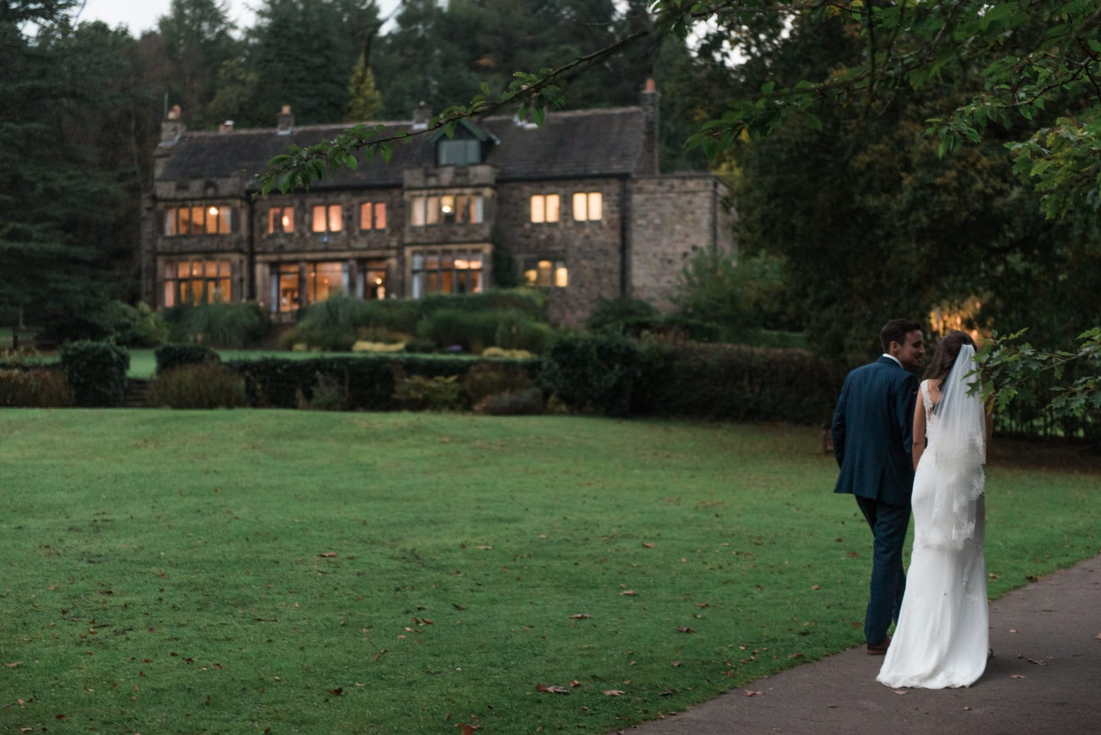 Bride and groom walking together at sunset outside Whirlowbrook Hall in Sheffield