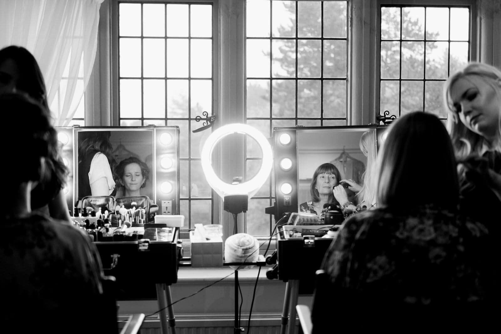 Bride and um getting make up done in front of mirror with lights around at Whirlowbrook Hall
