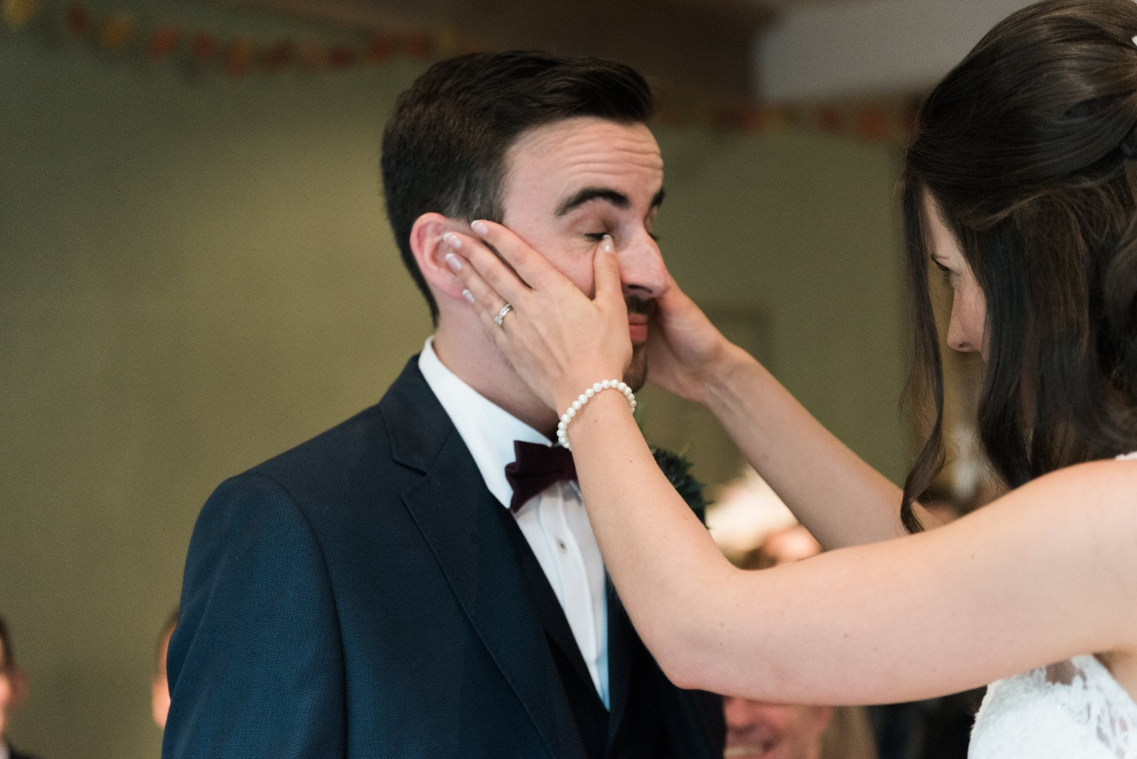 Bride wiping tears away of her groom at Whirlowbrook Hall wedding ceremony