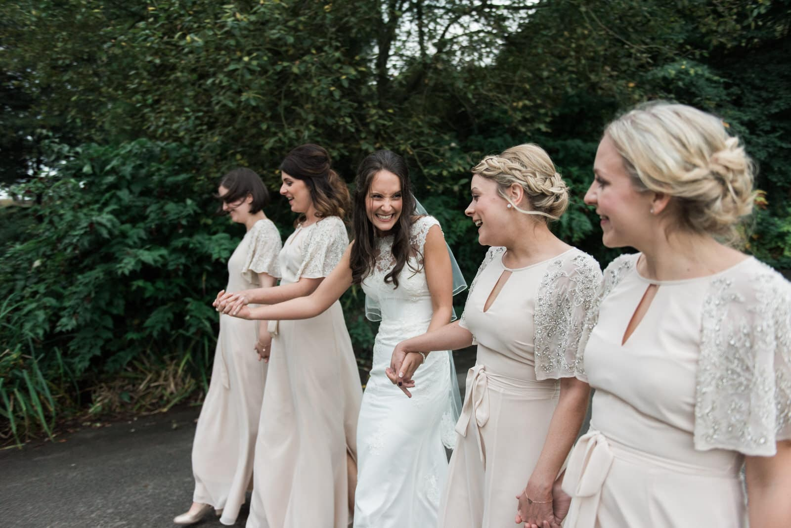 Bride walking with her bridesmaids in the grounds of Whirlowbrook Hall