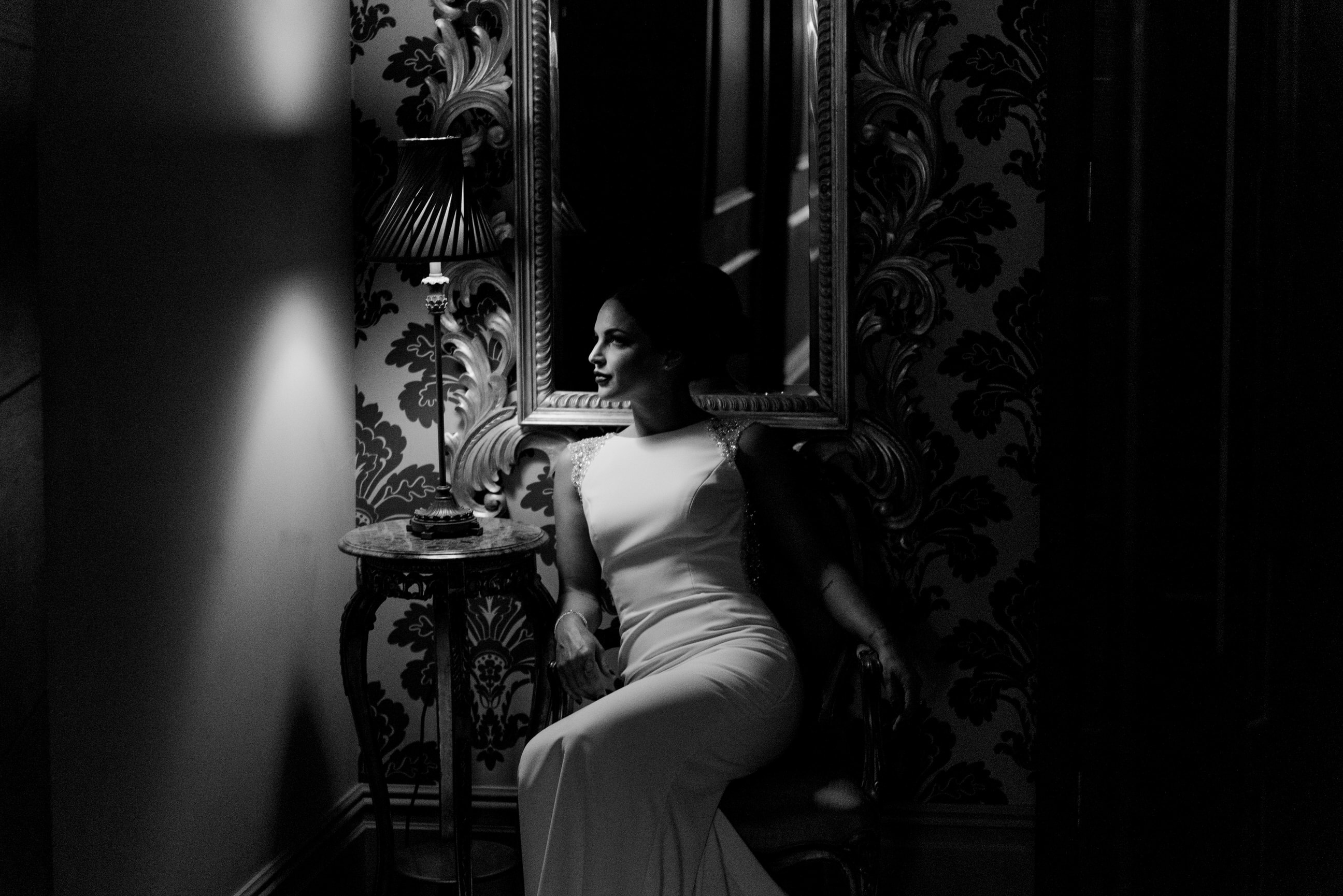 Bride sat in a chair in dramatic lighting