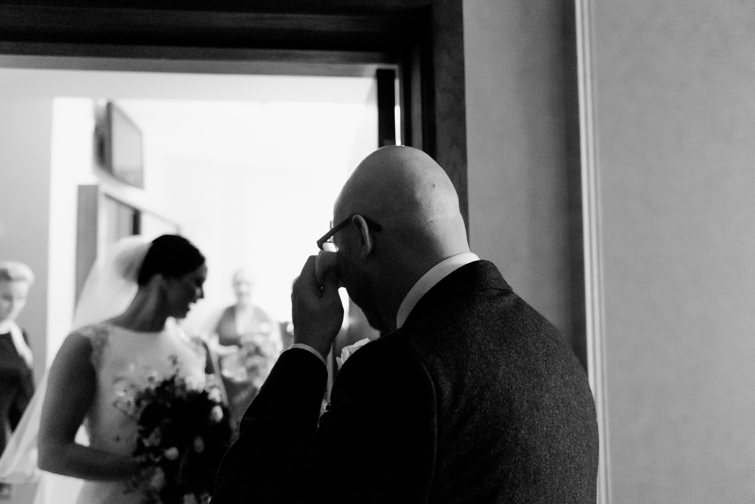 Groomsmen wiping away tear looking at bride