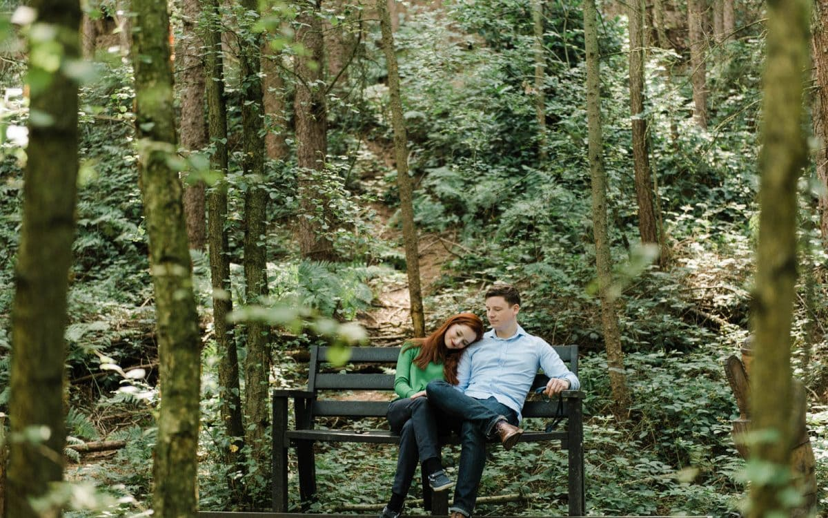 Couple in green woodland for engagement photo shoot