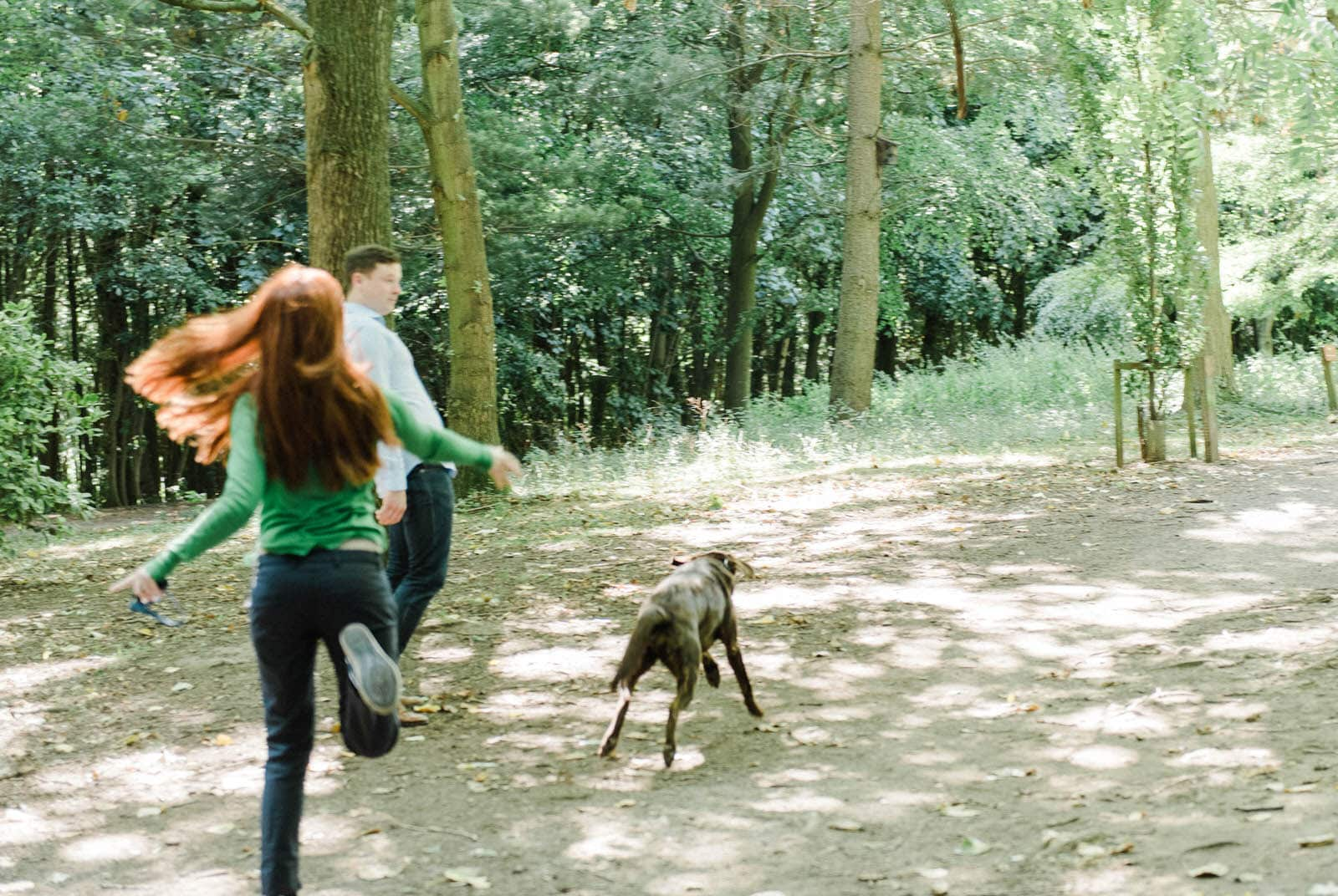 Couple throwing sticks for their dog on their engagement shoot at Newmillerdam