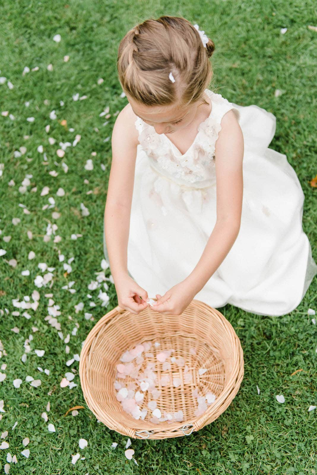 Flower girl putting confetti into a basket in the gardens of Oaklands Hall Hotel