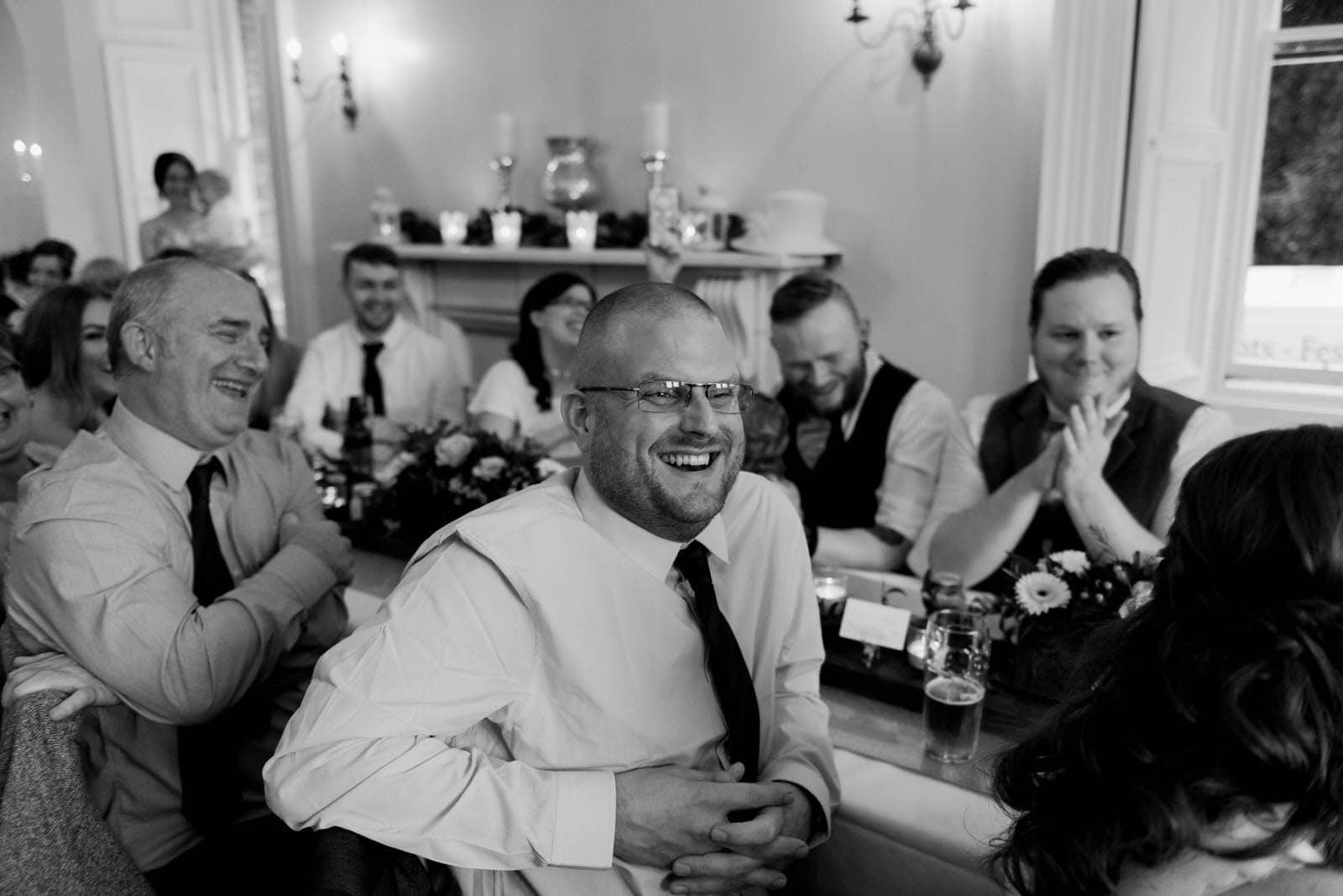 Wedding guests laughing at wedding speeches