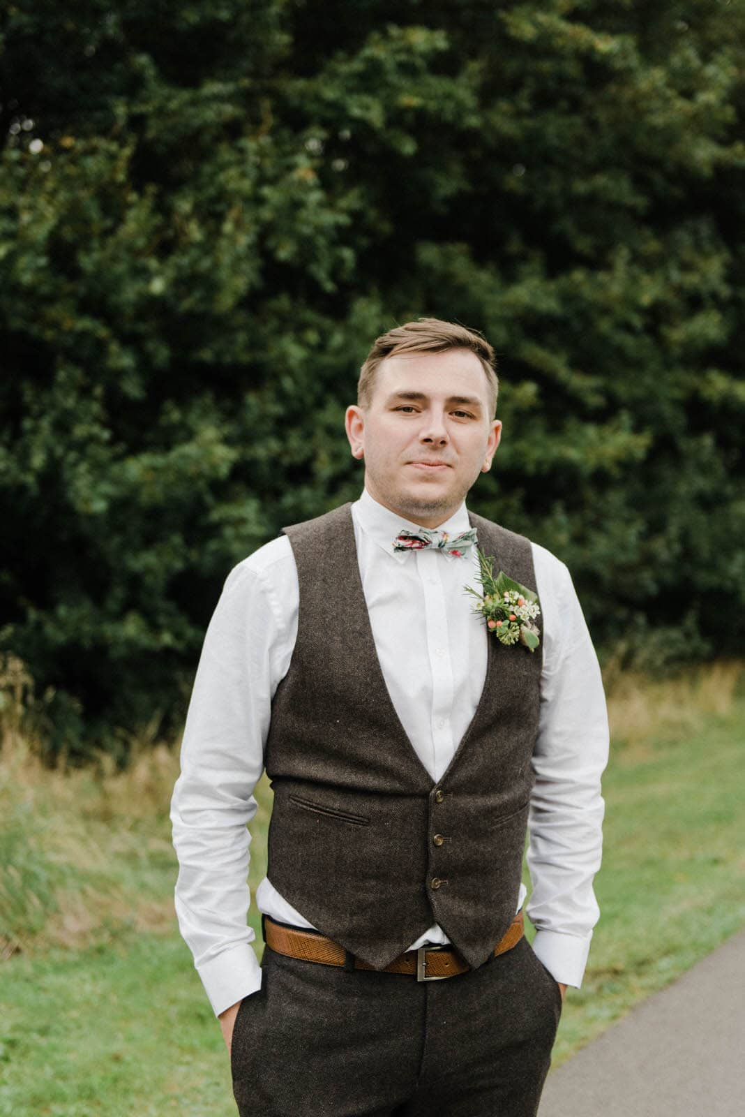 Portrait of the groom wearing brown tweed trousers and waistcoat, Colourful flower bowtie and flower button hole
