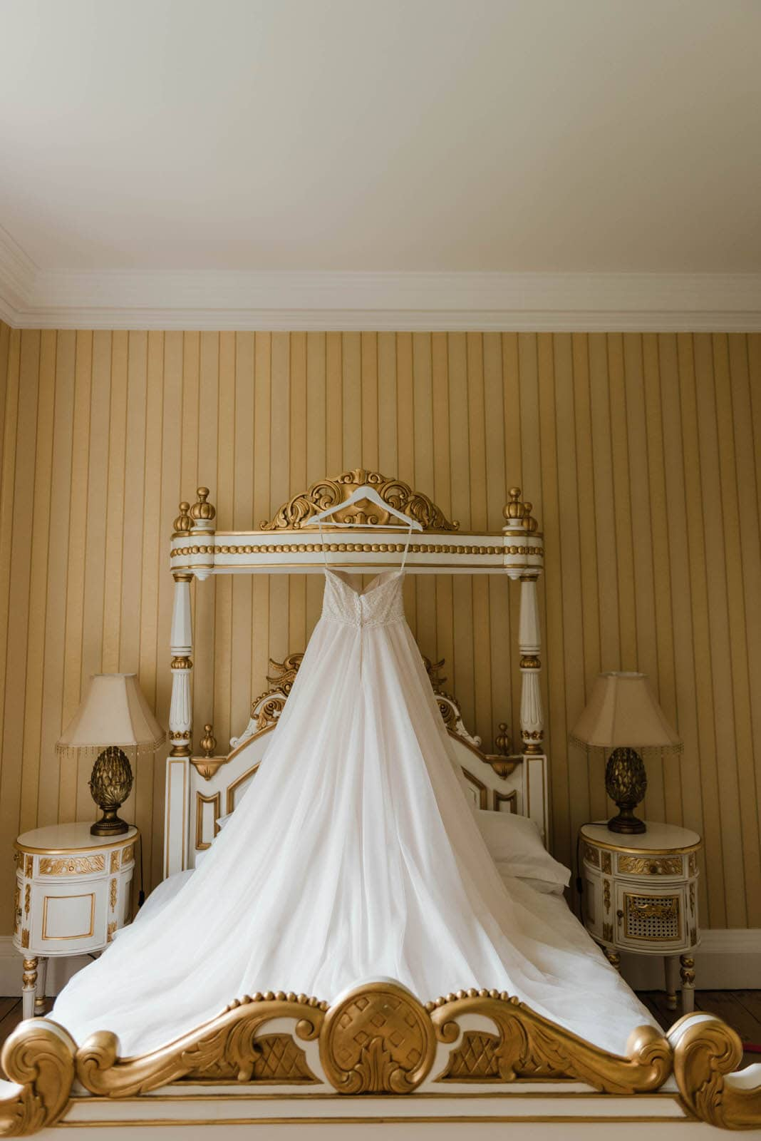 Photograph of beautiful wedding dress at Hirst Priory hanging on the bed