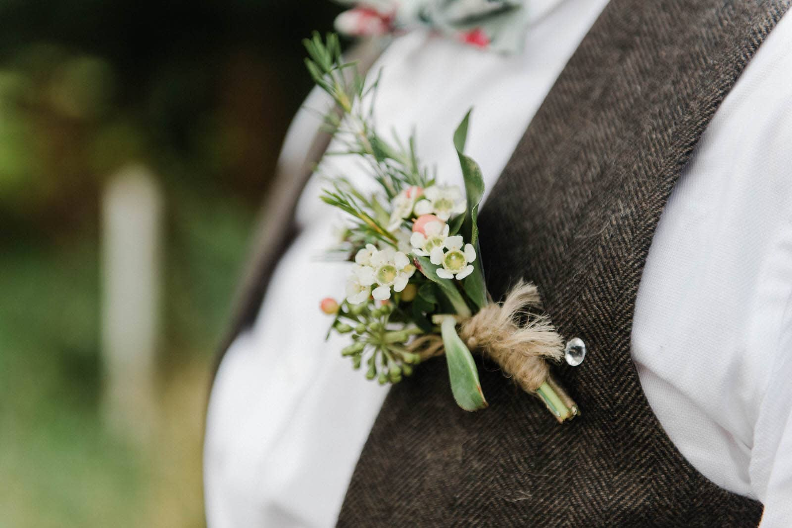 Close up photograph of a beautiful flower button hole on the groom