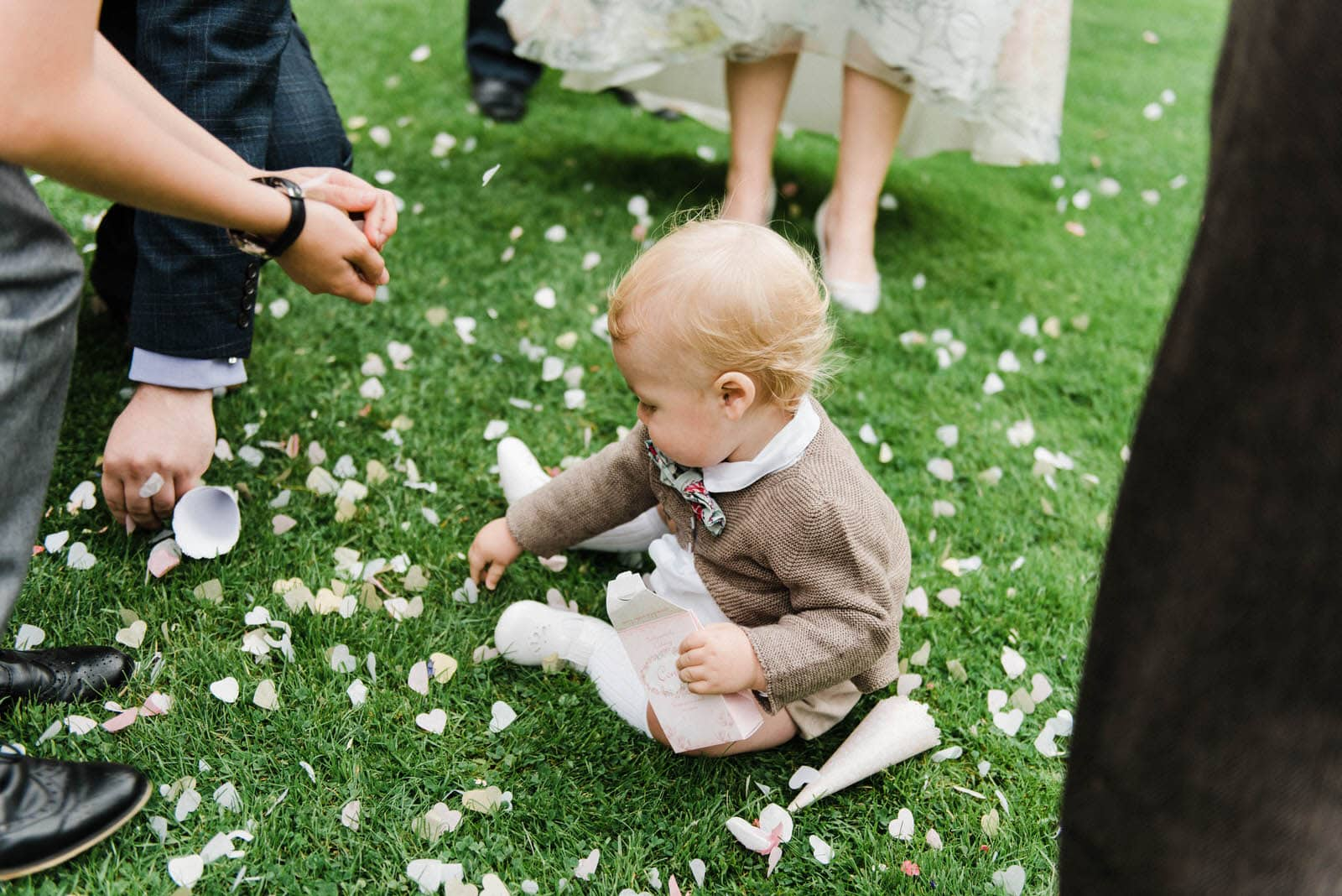 Baby sat on the grass picking up confetti at a wedding at Hirst Priory