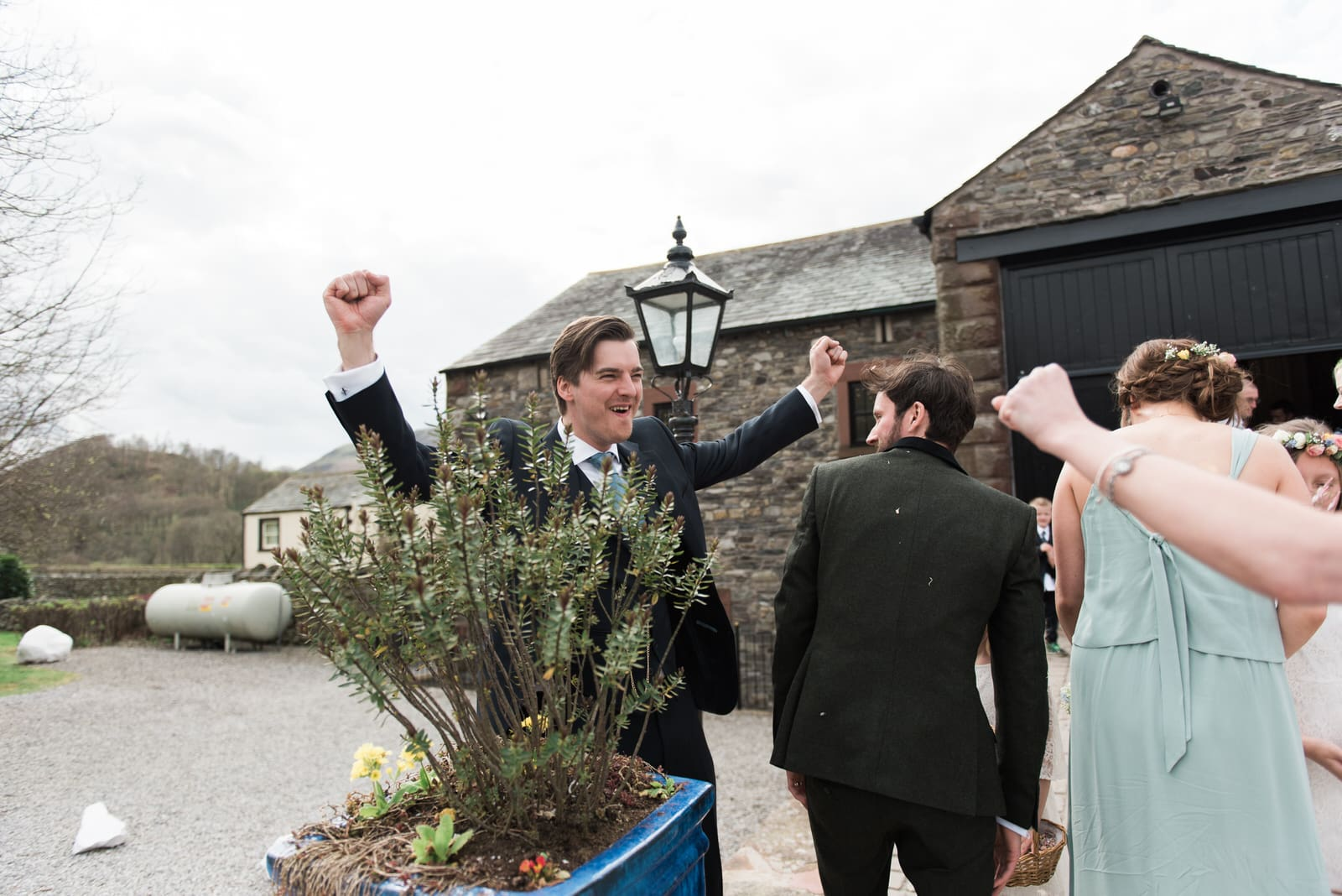 man cheering after wedding in the lake district