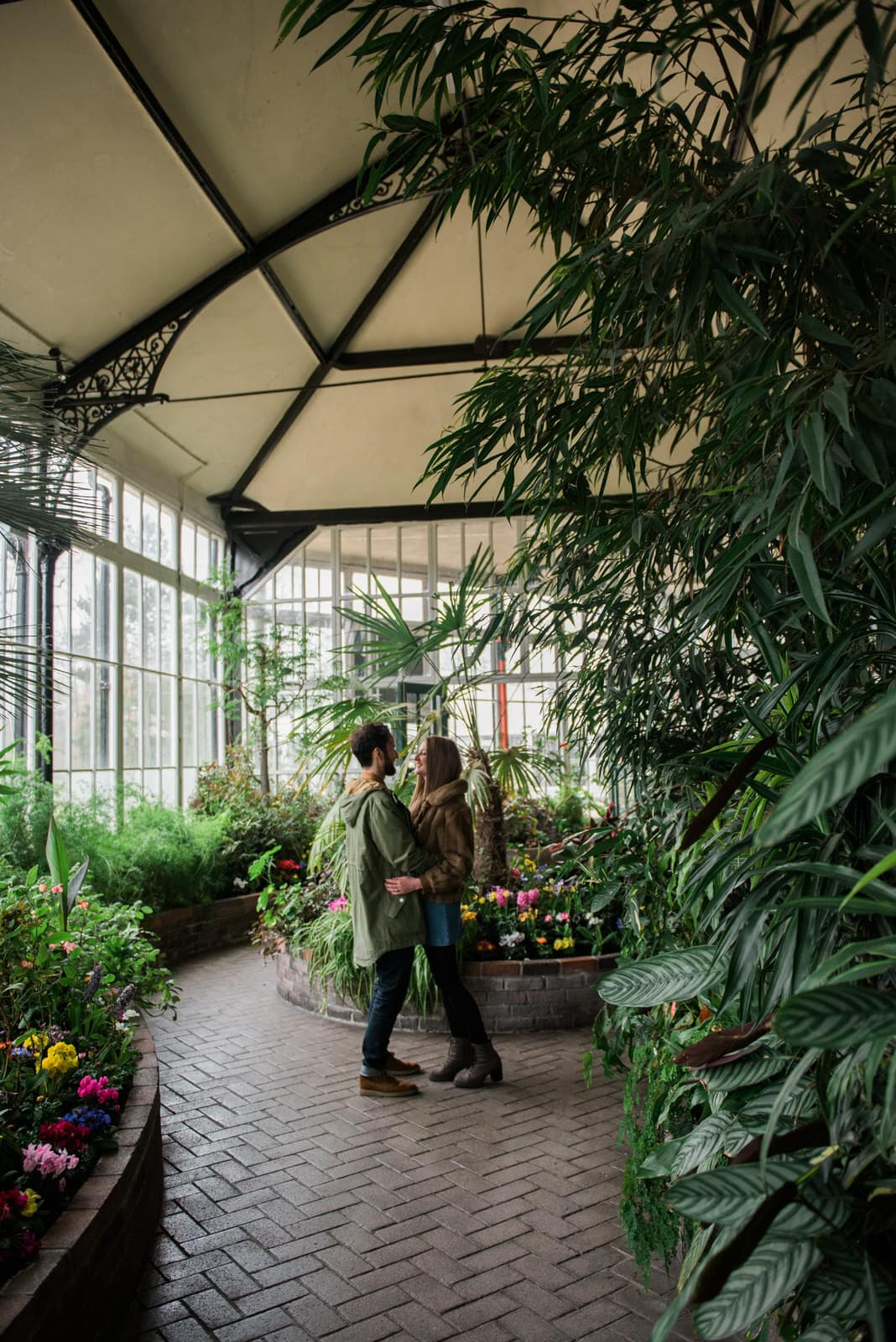 Couple stood in botanical gardens greenhouse