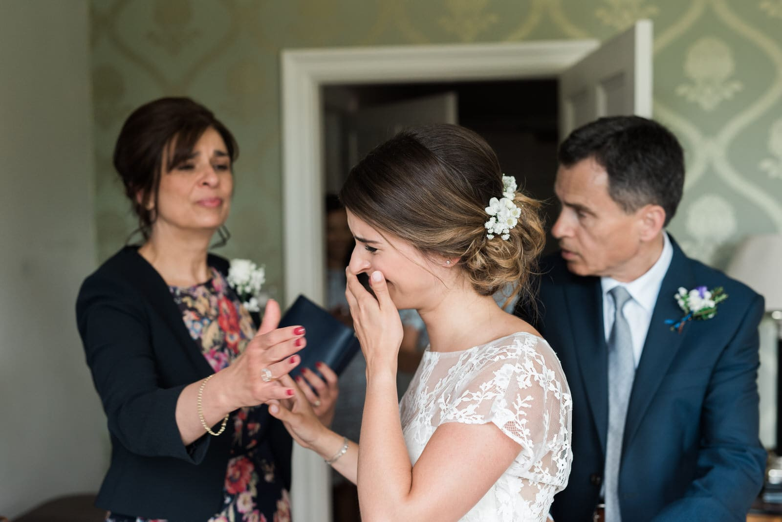 Wedding photograph of bride crying with her parents