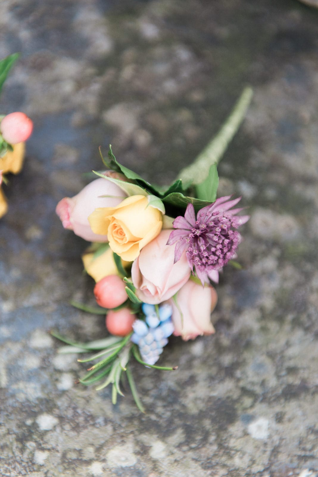 Grooms boutonniere laid on stone wall