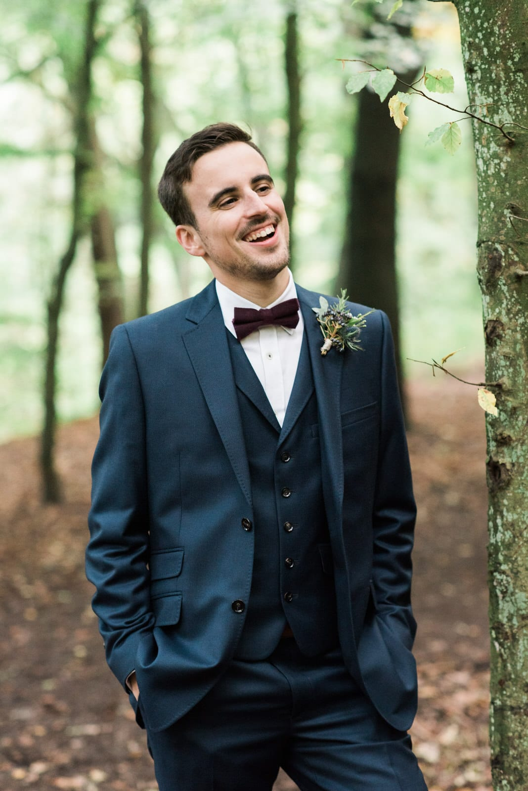Groom portrait in blue suit laughing