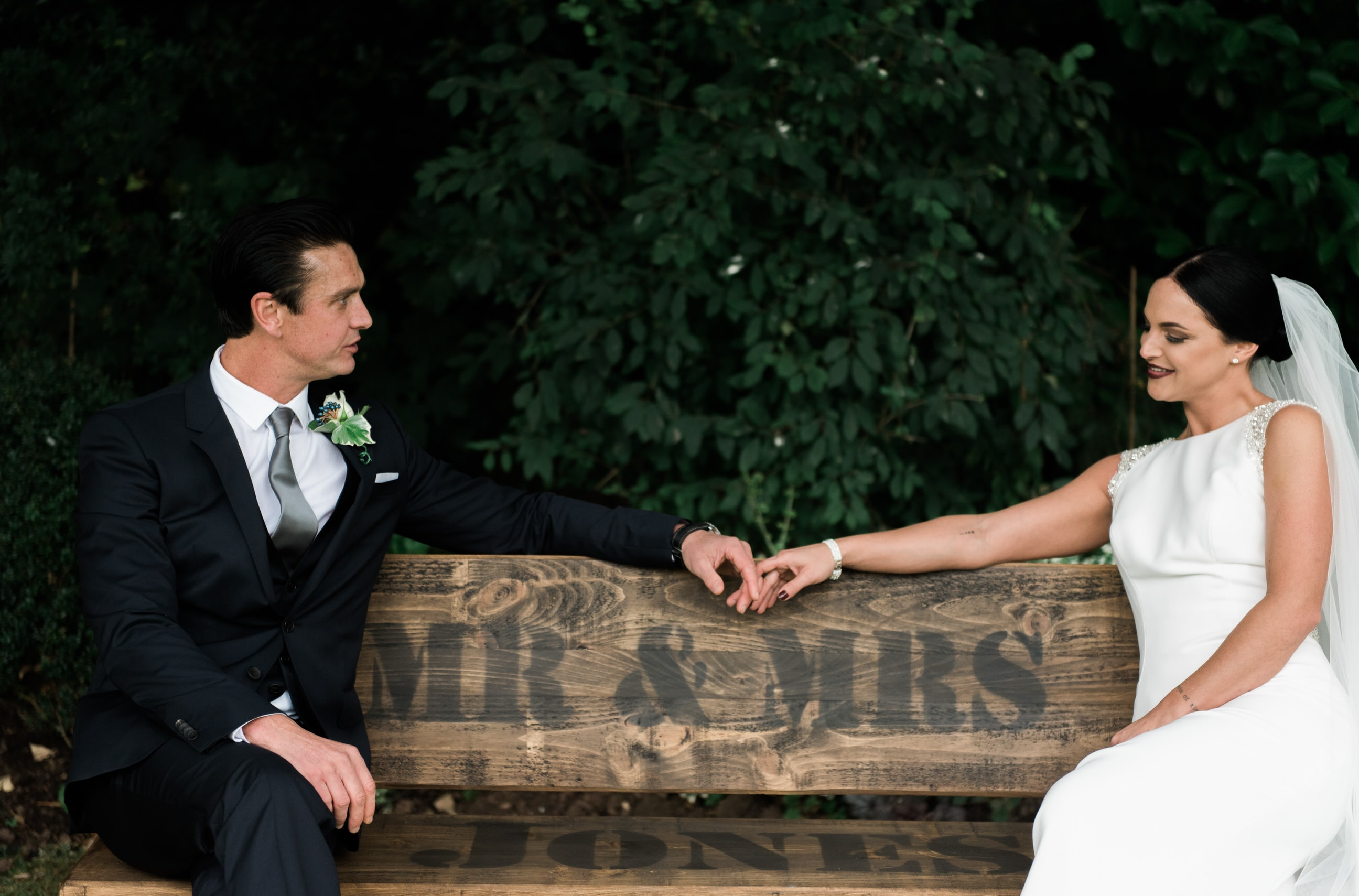 Bride and groom sat on a bench holding hands
