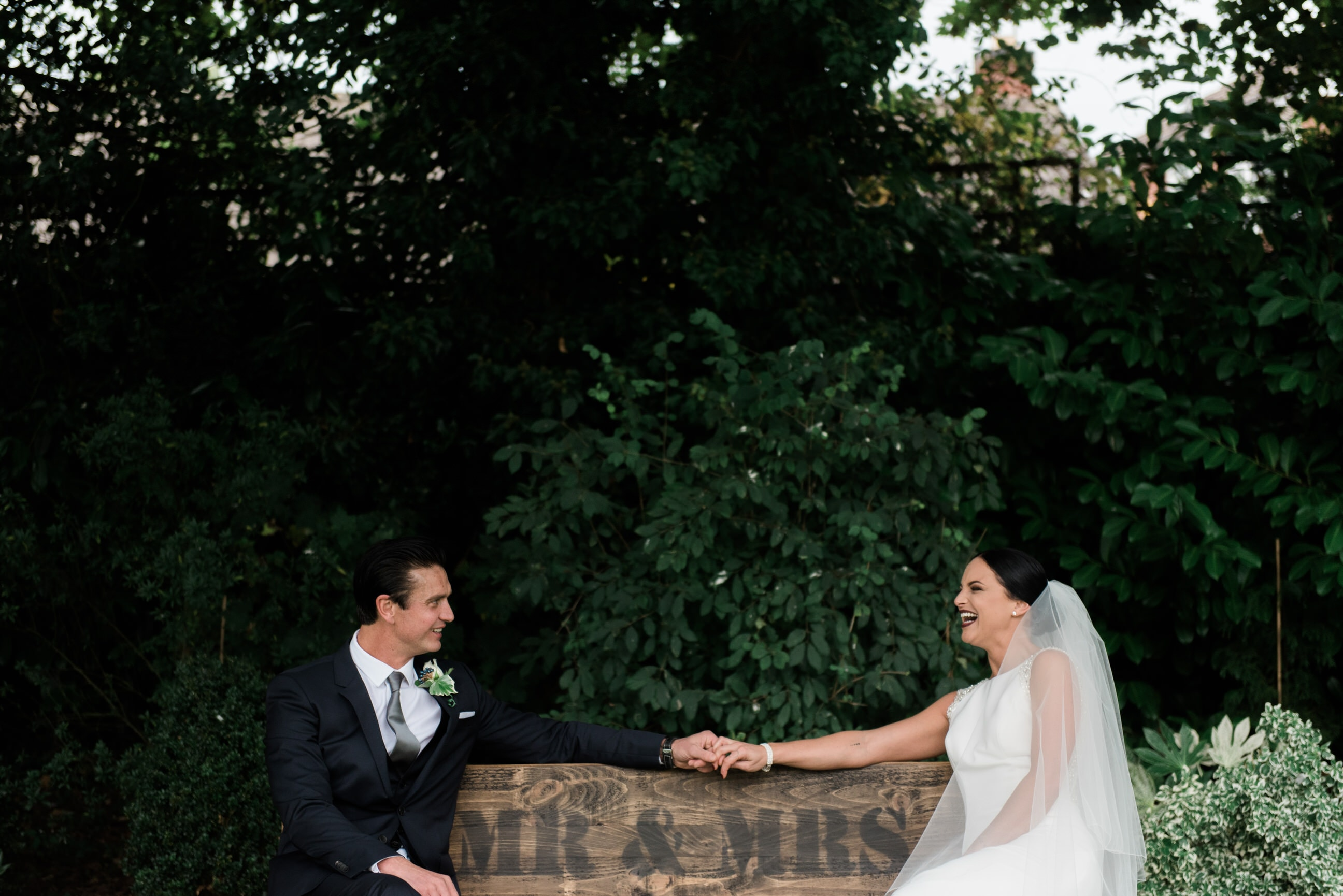 Bride and groom sat on bench laughing together
