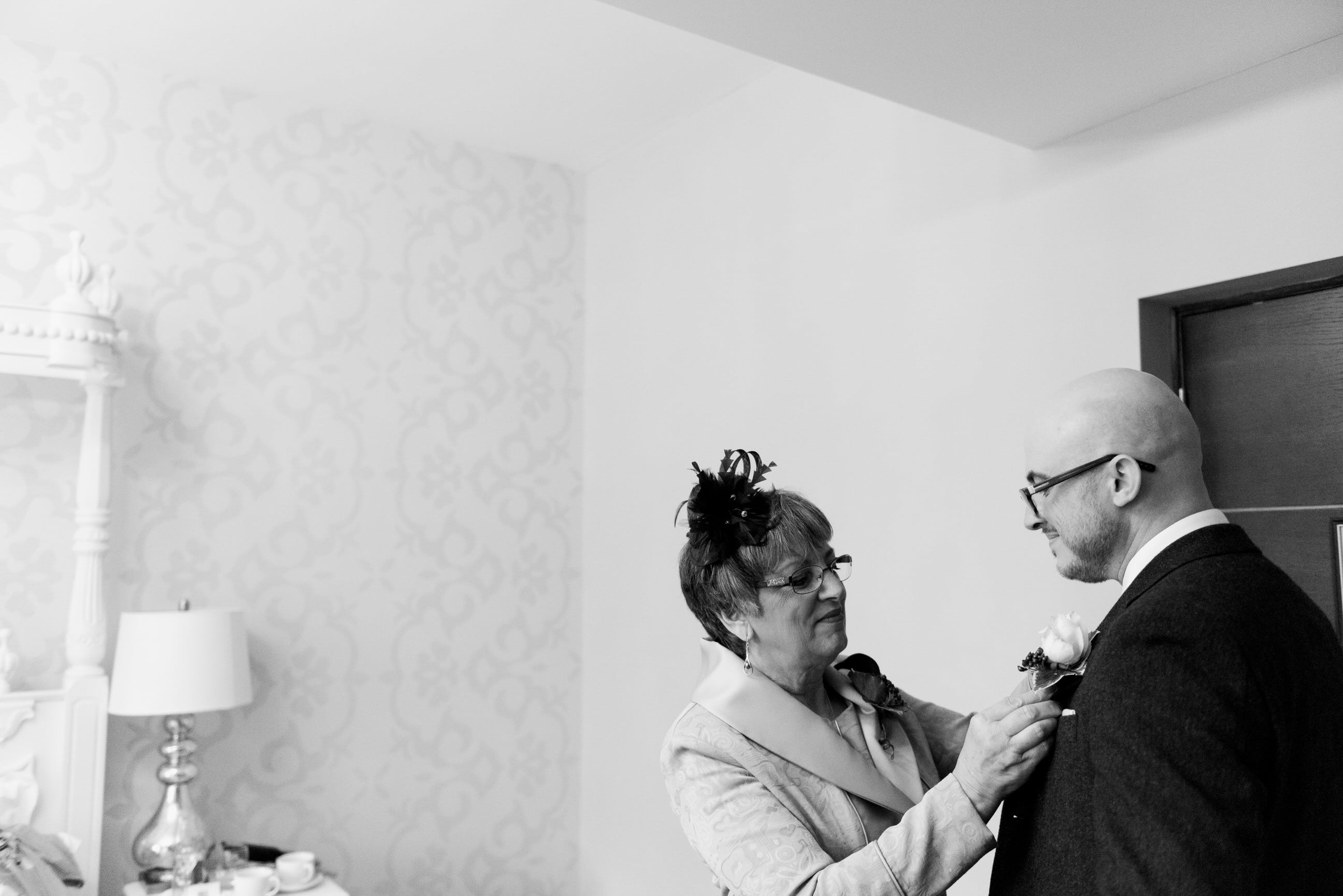 woman putting boutonniere on a man