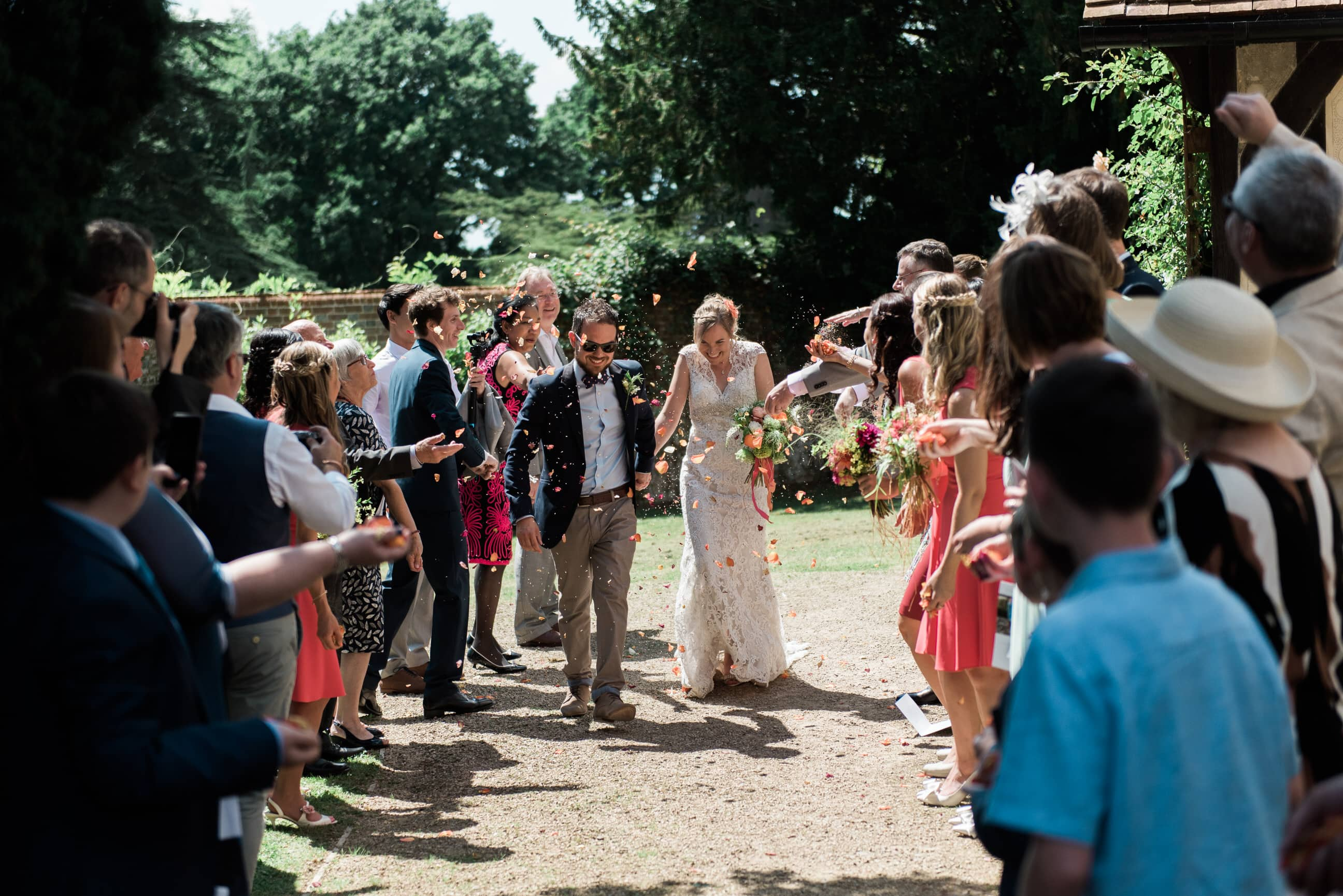 Bride and groom walking through a confetti throw in Surrey