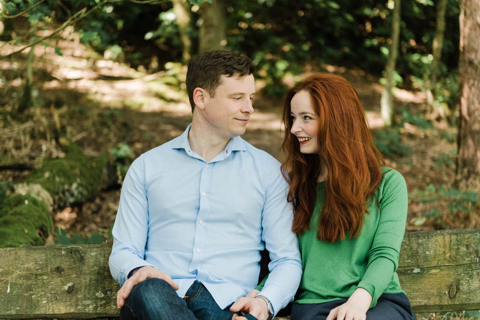 Beautiful portrait of a couple sitting on a bench surrounded by woodland at Newmillerdam