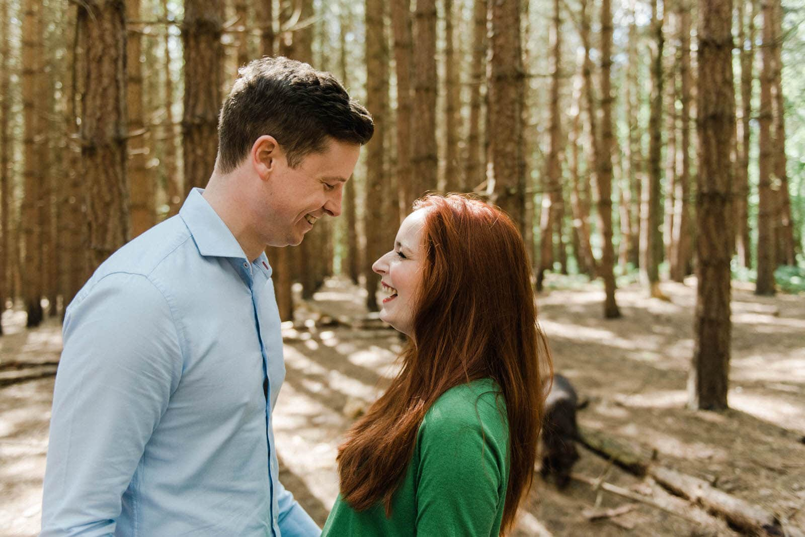 Couple laughing at each other during an engagement photo shoot in Yorkshire