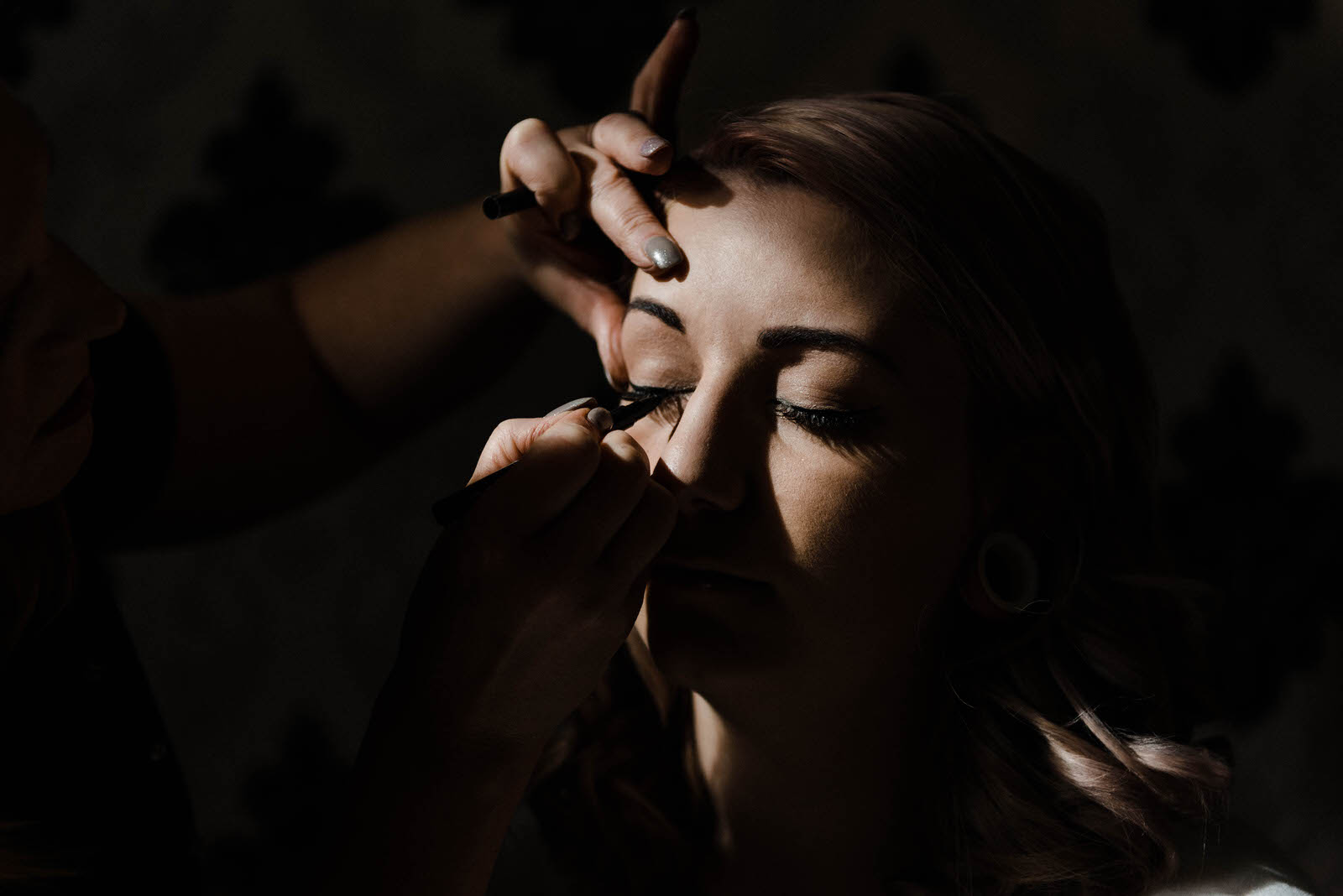 Photograph of bride getting her make up done at a Winter wedding at Hirst Priory