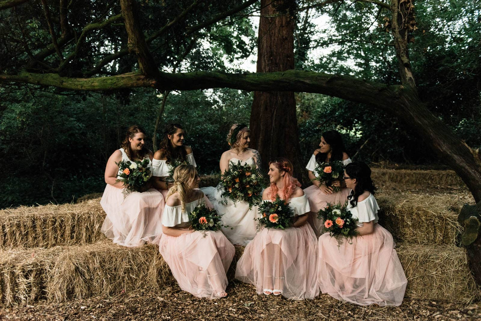 Bride sat with her bridesmaids outside on hay bales at Hirst Priory, Lincolnshire wedding