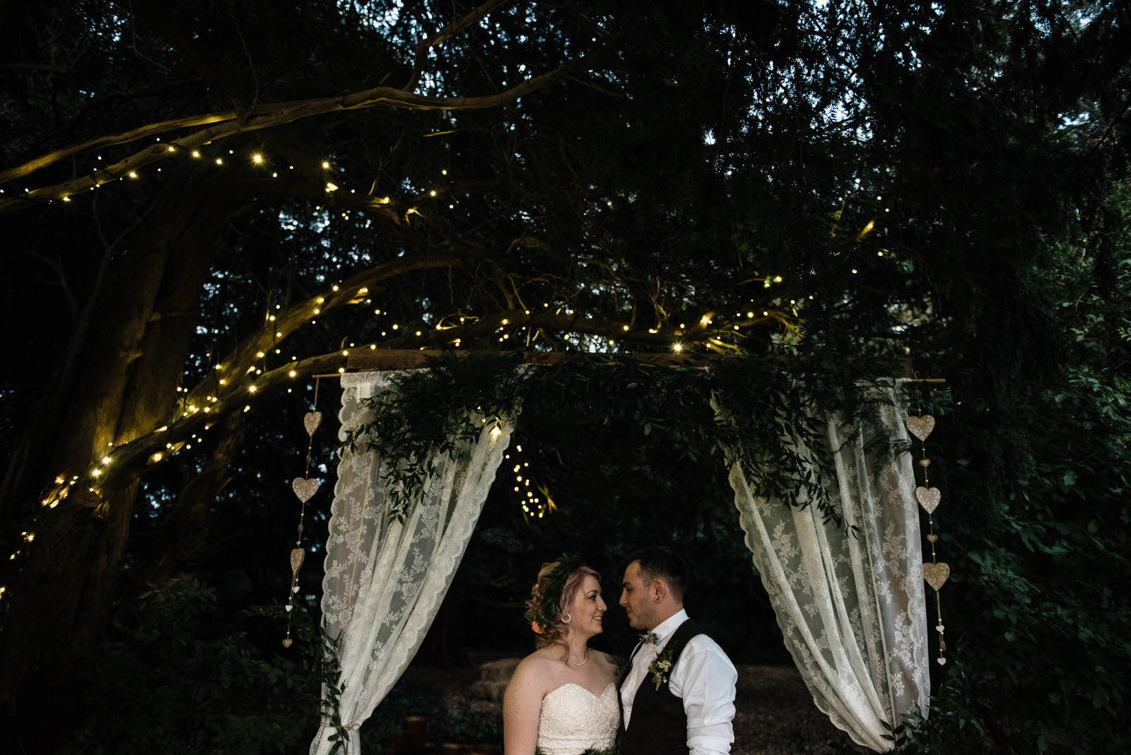 Bride and groom outside under twinkly lights in a wooded area of Hirst Priory