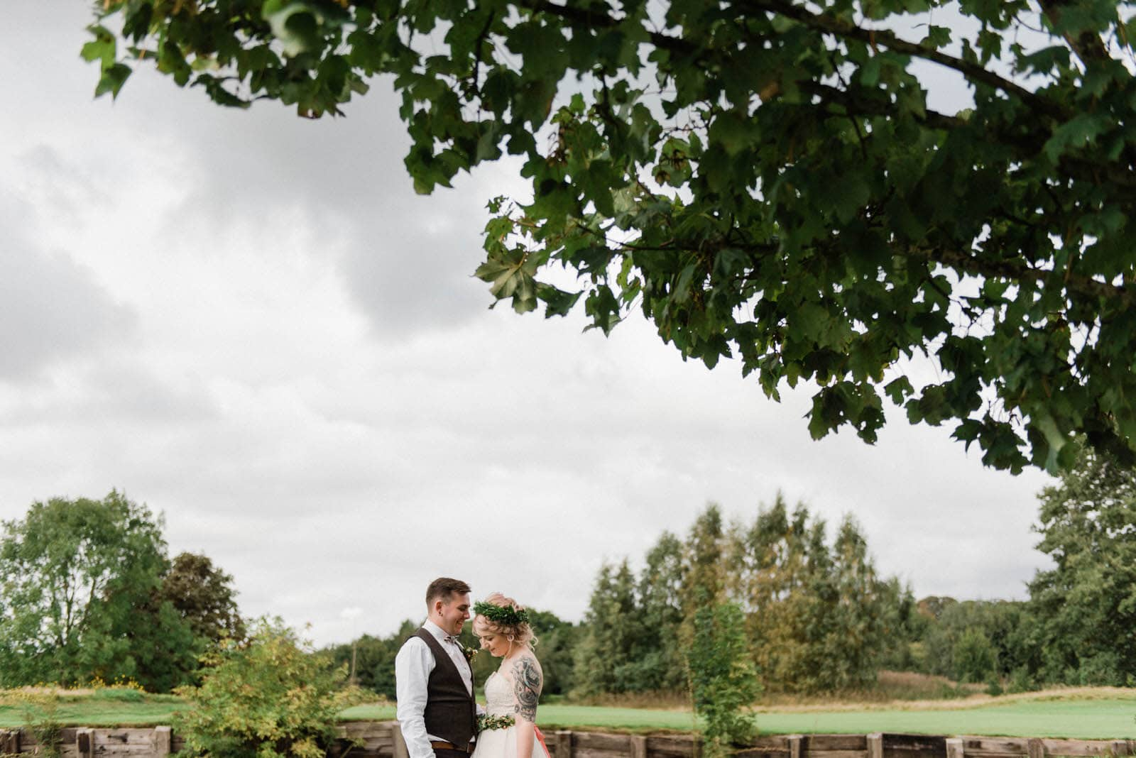 Bride and groom close together under a beautiful tree in the shade at Hirst Priory wedding