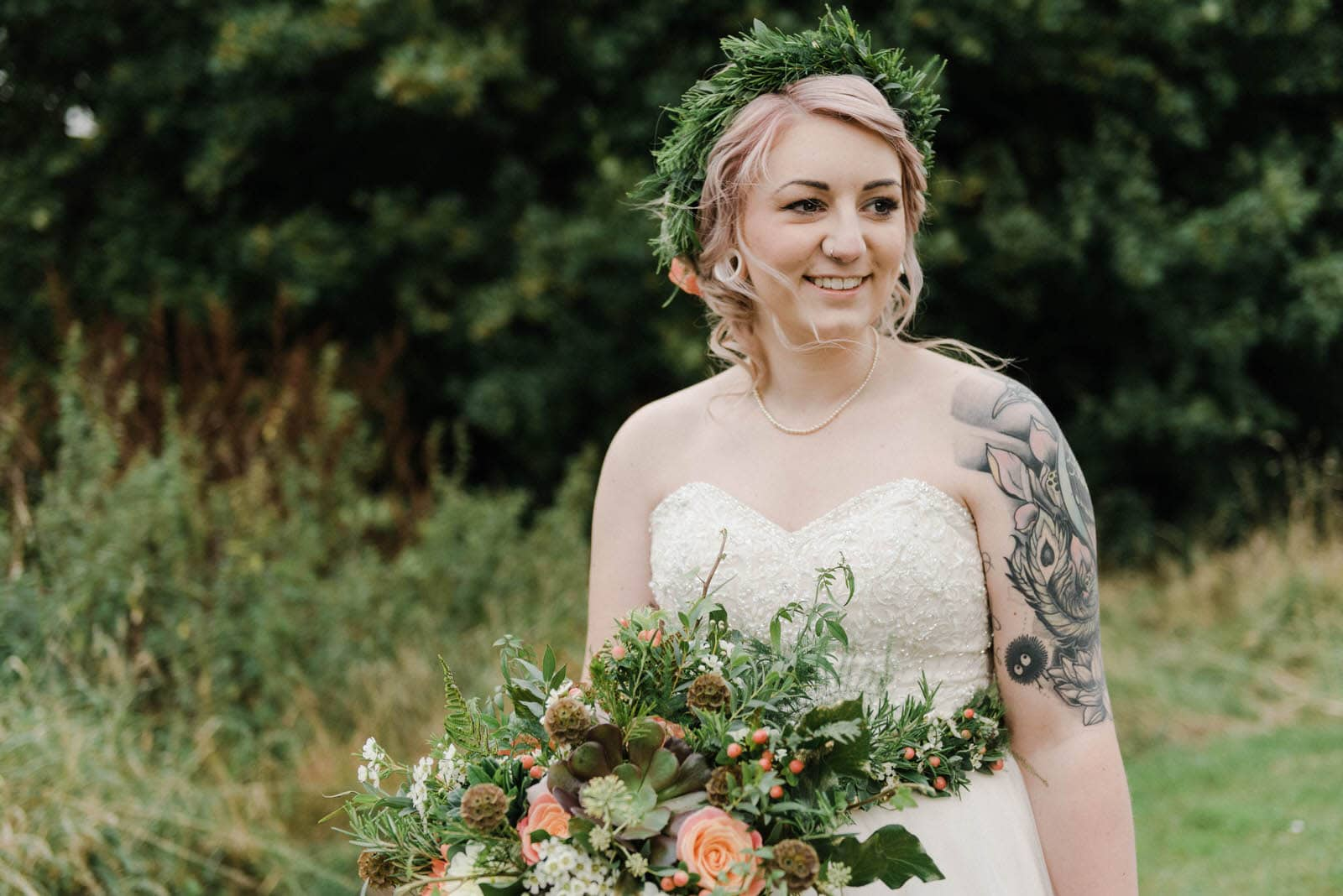 Beautiful portrait of a tattooed bride with pink hair wearing a flower crown and a flower belt