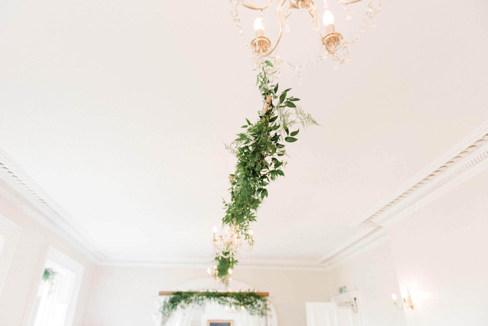 Chandeliers inside decorated with greenery and foliage at Hirst Priory wedding