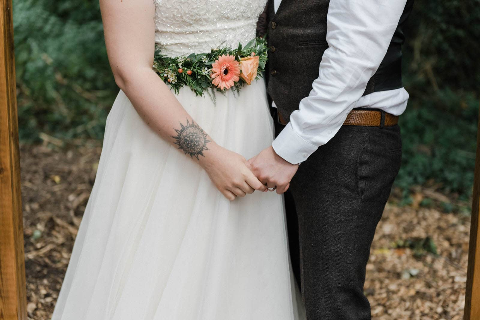 Bride wearing a flower belt and groom holding hands under a woodland area in Hirst Priory.