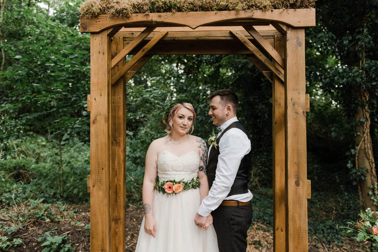 Bride and groom under a wooden archway in a woodland area at Hirst Priory Wedding