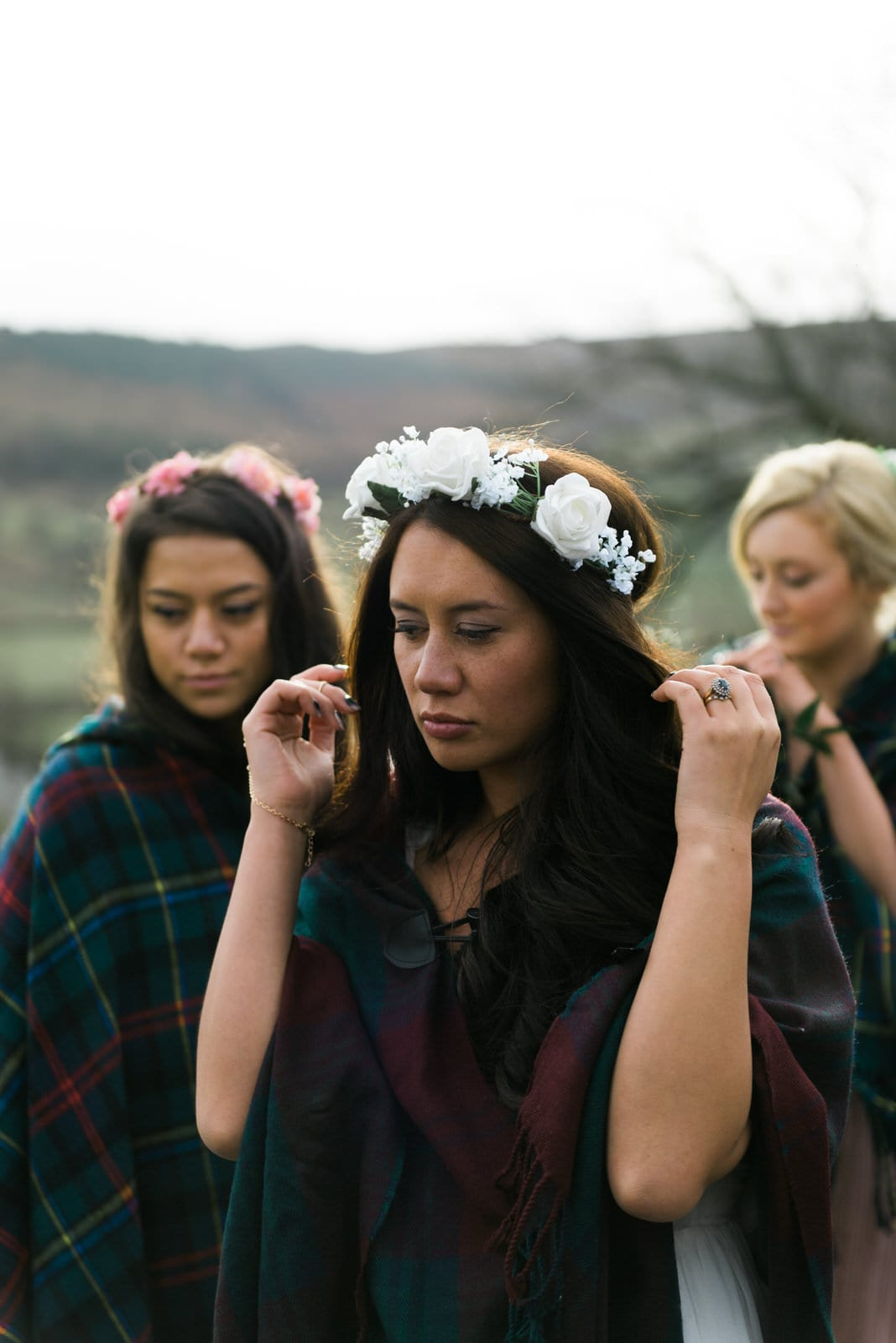 Bride with her bridesmaids wearing flower crowns and blankets