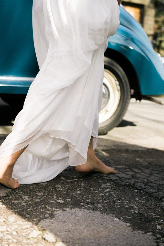 close up of barefoot bride walking on pavement