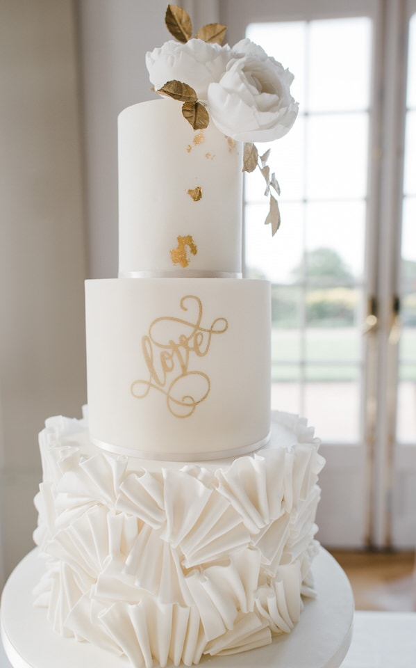 white ruffle wedding cake with gold LOVE writing