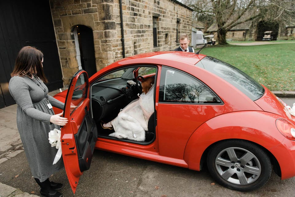 Bride getting out of red VW beetle car