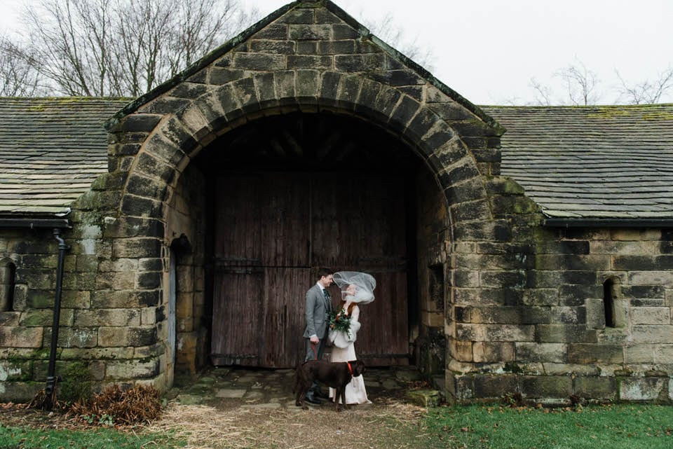 Bride & groom portrait in stone arch with dog