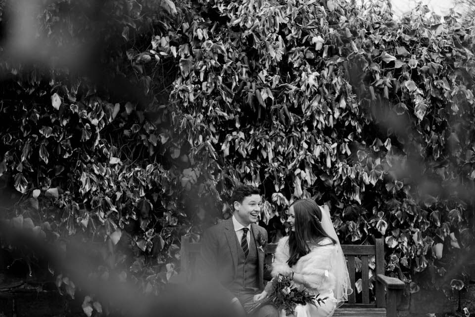 black and white image of bride and groom on bench
