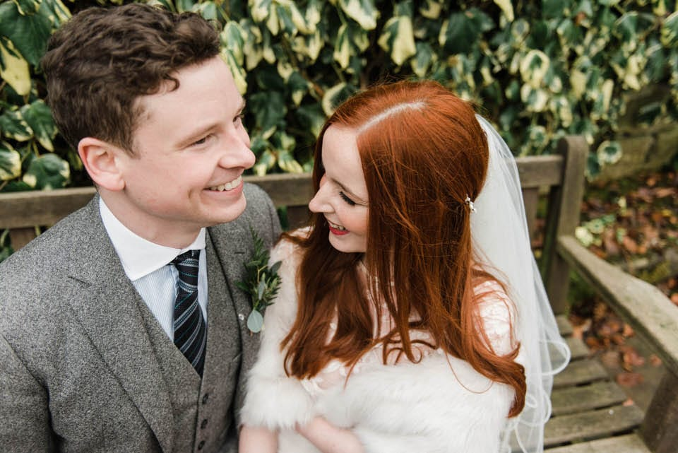 red head bride and groom on bench at yorkshire wedding venue East Riddlesden Hall