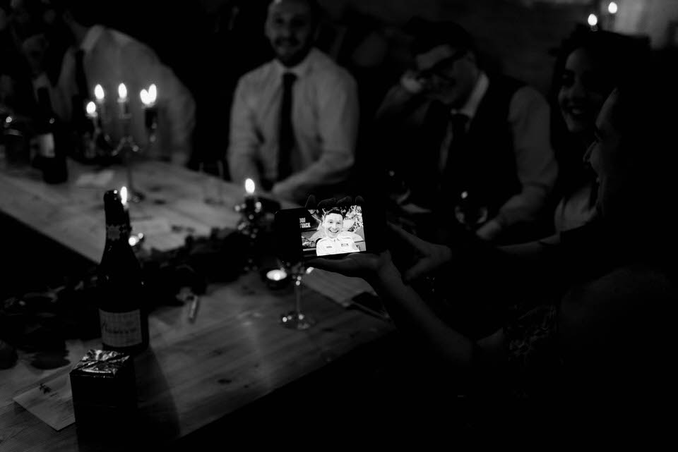 guests holding phone with groom picture