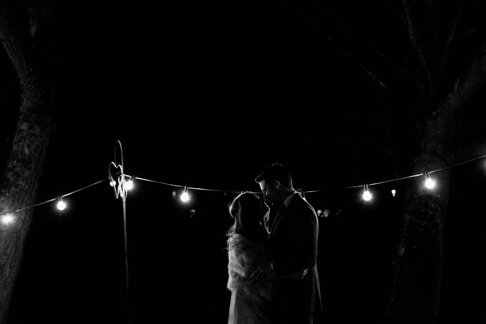 Bride and groom at night festoon lighting