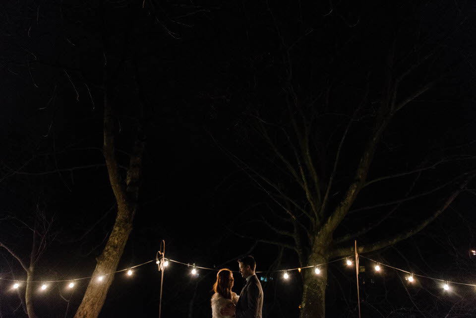 Bride and groom at night with festoon lighting