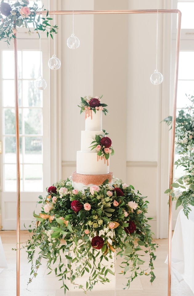 white wedding cake inside a copper frame with real flowers