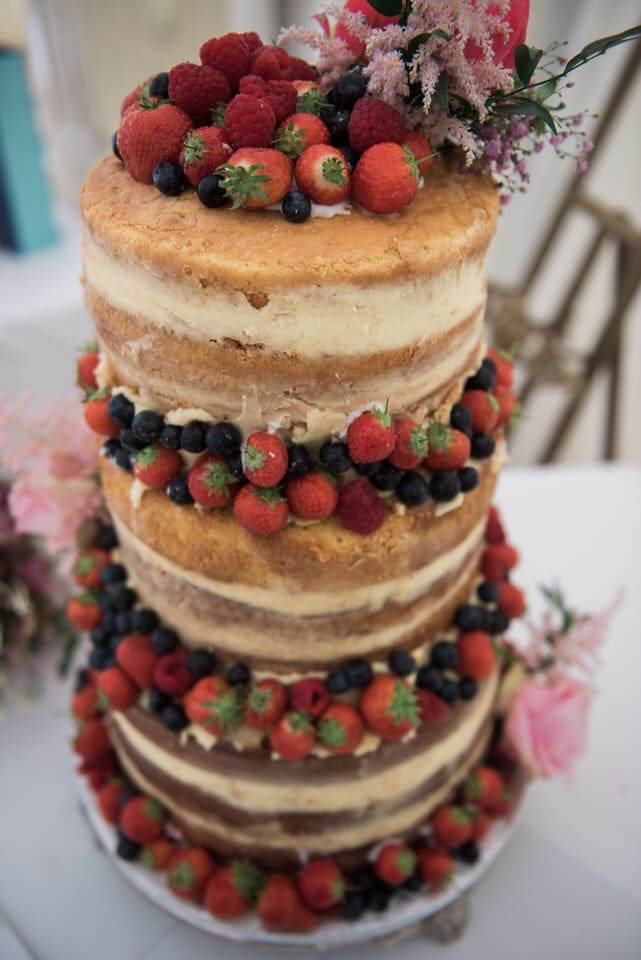 naked wedding cake decorated with fruit and berries