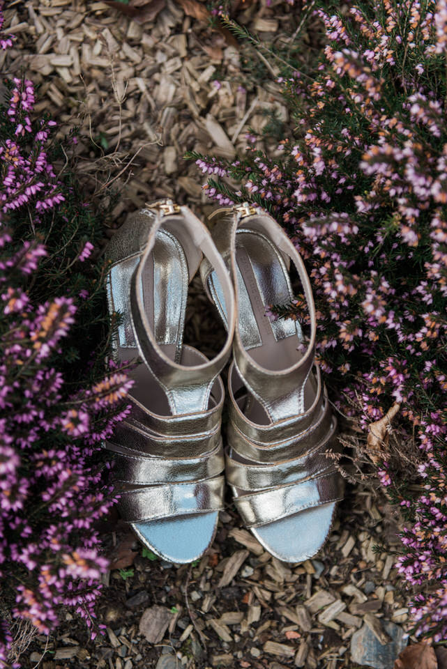 gold wedding shoes in a bed of purple flowers