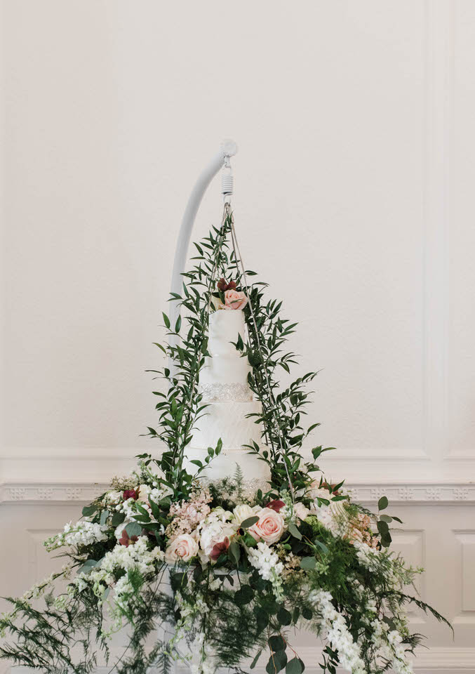 White wedding cake hanging from a white frame with flowers and greenery