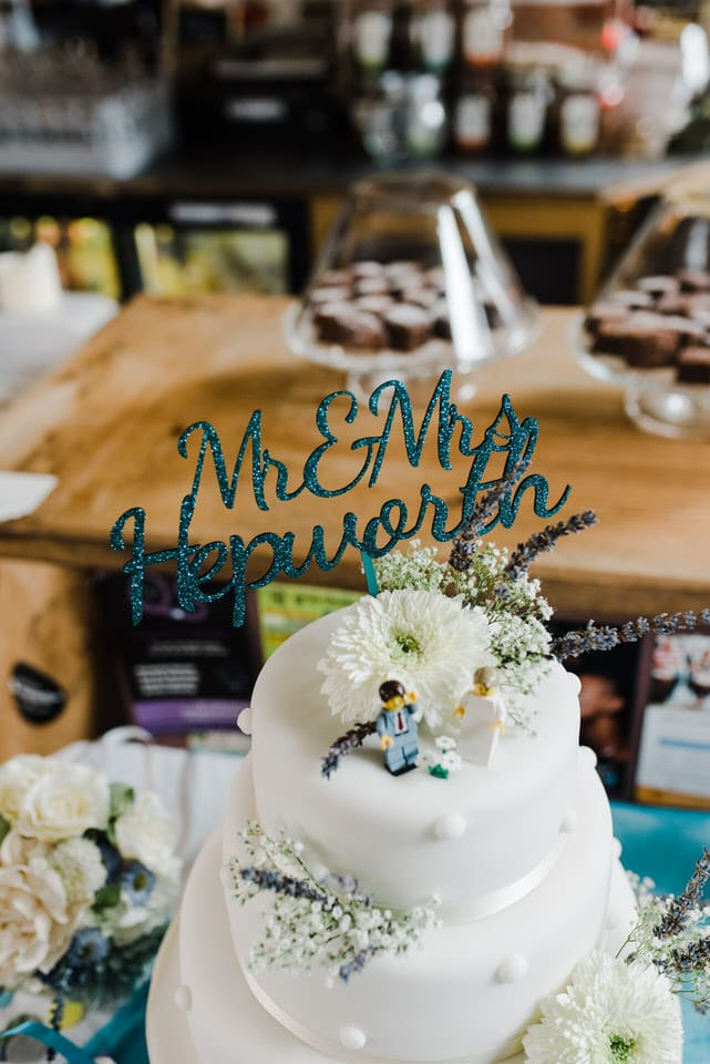 white iced wedding cake with blue cake topper and lego figures